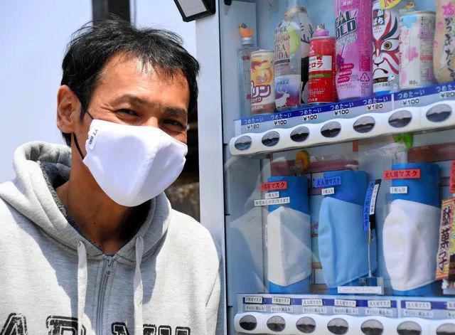 Goto đứng trước máy bán hàng tự động cùng loại khẩu trang đóng băng của mình.