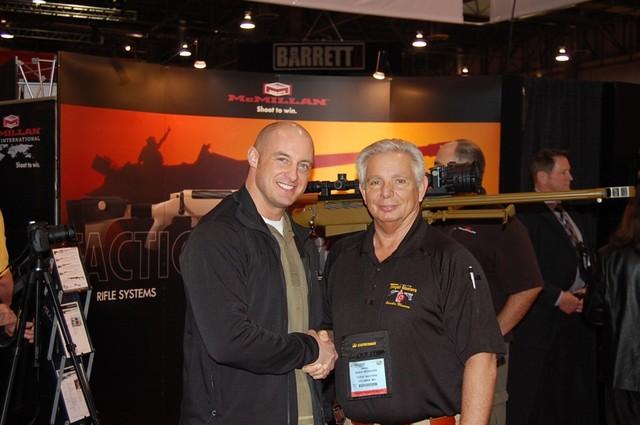 Rob Furlong đứng bên người đại diện và khẩu MacMillan Tac-50R2 huyền thoại của mình (phía sau) tại triển lãm năm 2009 của MacMillan.