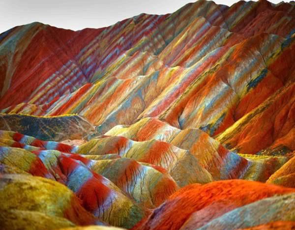 Nhiều người sẽ không tin dãy núi đầy sắc màu trong ảnh tồn tại, nhưng nó đang hiện diện ở. Công viên Địa chất Zhangye Danxia, tỉnh Cam Túc, Trung Quốc. Nó hình thành do qua trình nén các lớp sa thạch và khoáng chất nhiều màu trong suốt 24 triệu năm. Gió và mưa tiếp tục hoàn thành công việc tạo hình cho các núi đá, khiến chúng có nhiều hình dạng khác nhau như cột, thung lũng, khe núi, thác nước.