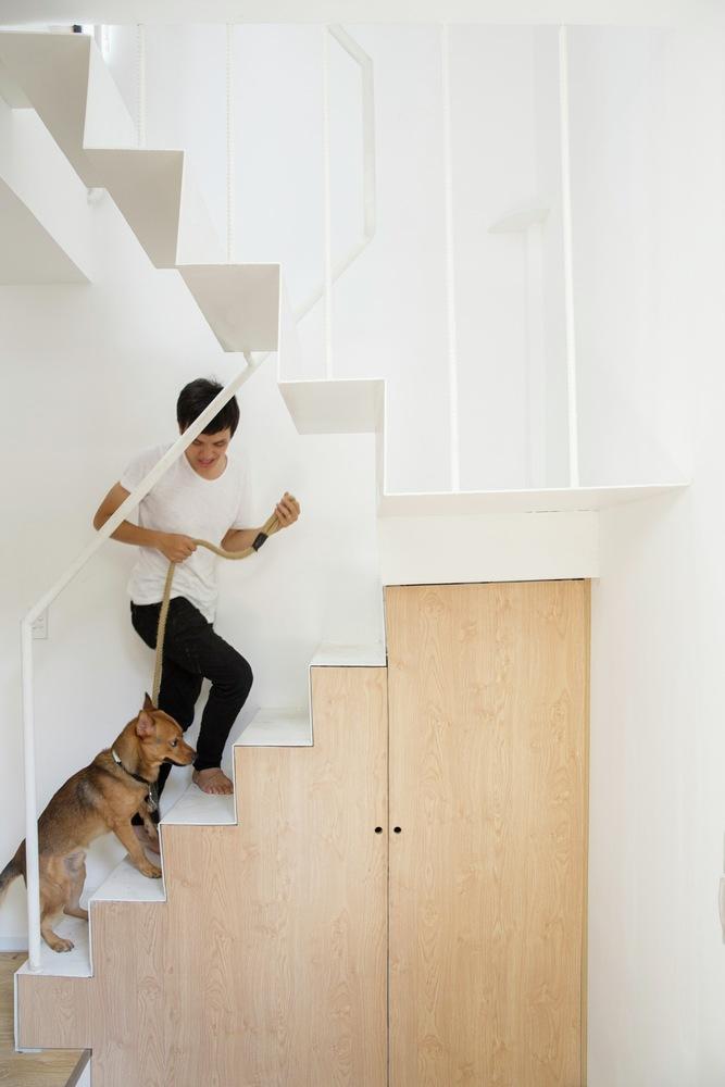 Cầu thang lên xuống đơn giản, không gian bên dưới được sử dụng làm tủ chứa đồ