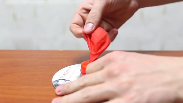 Bây giờ bạn hãy đặt phần đầu của bong bóng vào bên ngoài của nắp chai nhựa.