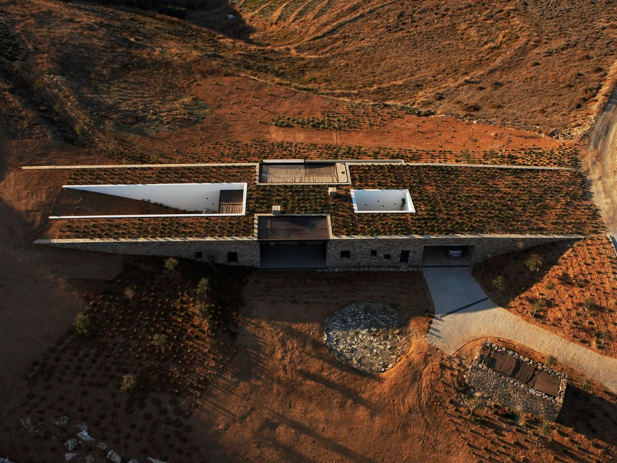 Ngôi nhà này tọa lạc trên một hòn đảo thuộc Hy Lạp, giữa hai sườn đồi. Hai bức tường nối hai bên đồi lại, cho phép ngôi nhà nằm một cách tự nhiên ở giữa.