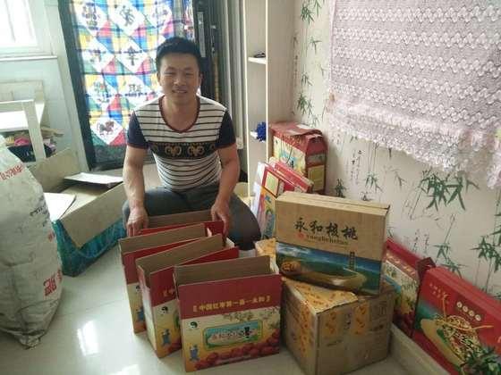 Liu Dongdong bên các thùng chà là đỏ đang chờ được ship đi