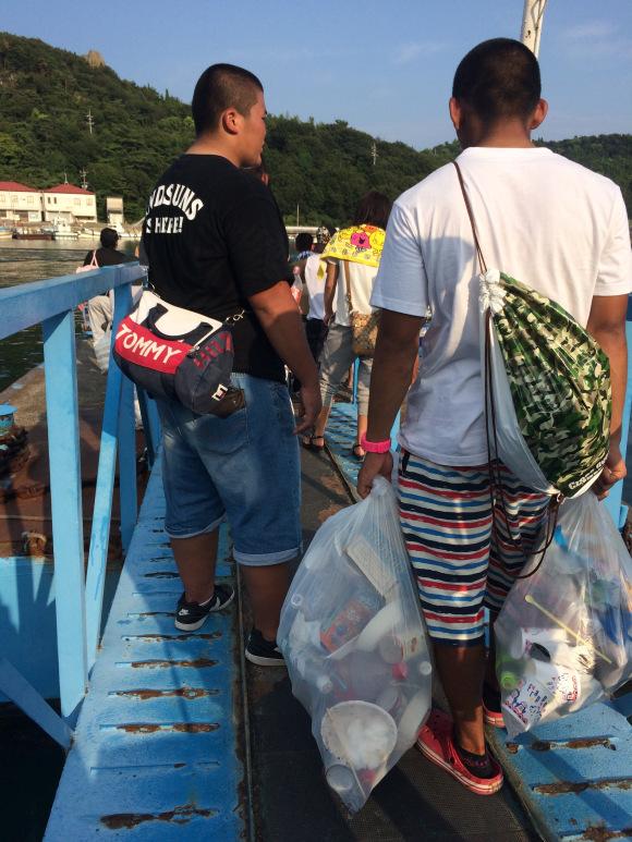 Hai người đàn ông mang túi rác của mình về sau bữa tiệc barbecue trên bãi biển Shiraishi.