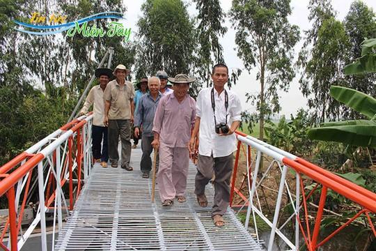Niềm vui của Ba Đạt (bìa phải) và người dân địa phương khi cầu hoàn thành.