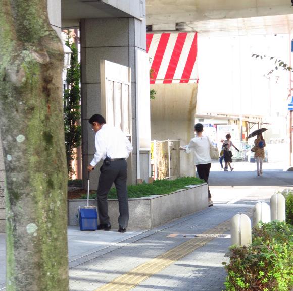 Một nhân viên đang quét dọn trước cửa văn phòng.