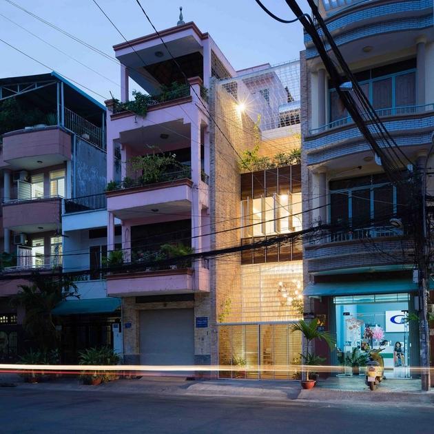 Ngôi nhà khi về đêm. Các thanh thép cùng ánh sáng khiến ngôi nhà trở lên nổi bật giữa những khối đặc kín xung quanh.