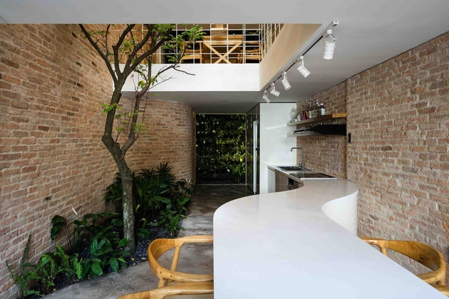 Phòng ăn với phần đảo bếp uốn lượn, giúp không gian có được sự mềm mại, cân bằng lại tính thô cứng từ vật liệu gạch và thép mang lại.