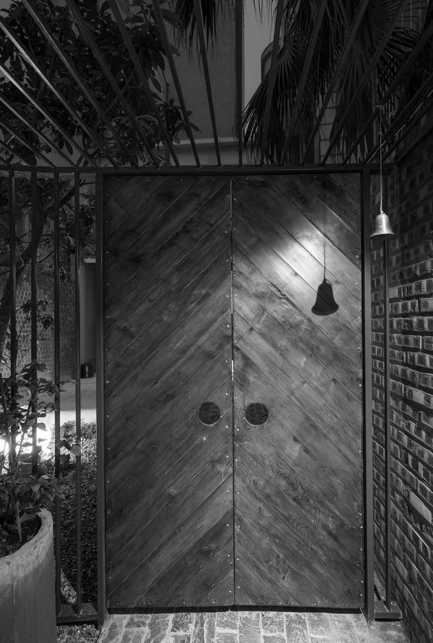 Cánh cửa bằng gỗ tự nhiên vời khung thép hộp duyên dáng.
