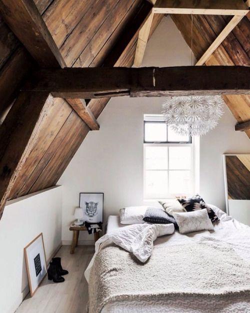 Một phòng ngủ với phần mái và kết cấu bằng gỗ, sơn tường vẫn là màu trắng chủ đạo.