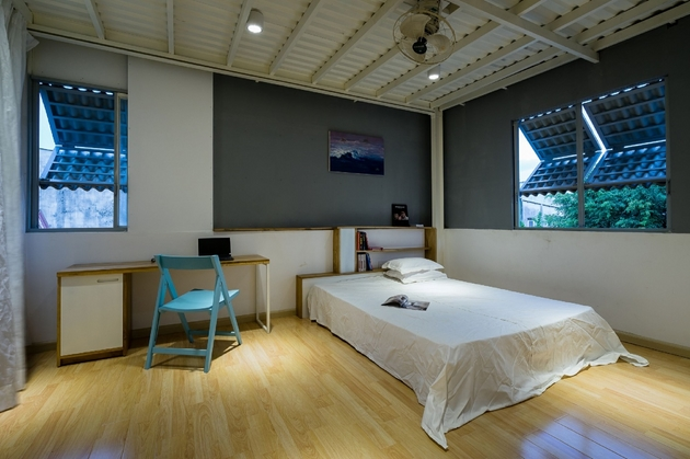 Phòng ngủ cho các con được thiết kế đơn giản. Toàn bộ đồ nội thất ( ngoại trừ ghế ngồi) đều được KTS thiết kế theo nhu cầu công năng và thẩm mỹ của gia chủ. Những tấm lợp oduline được biến hóa thành những ô cửa sổ gấp. Ưu điểm của loại cửa sổ này, đó là sự linh hoạt trong việc điều chỉnh ánh sáng và tránh mưa hắt.