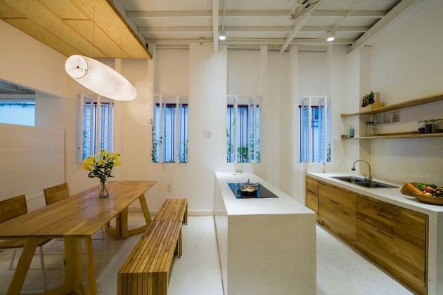 Khu bếp được thiết kế gọn gàng. Toàn bộ hệ tủ được đẩy xuống dưới bếp và bồn rửa. Trên các diện tường chỉ tồn tại hai đợt gỗ phục vụ công năng đơn giản, giúp không gian được sạch và thoáng về mặt thị giác.