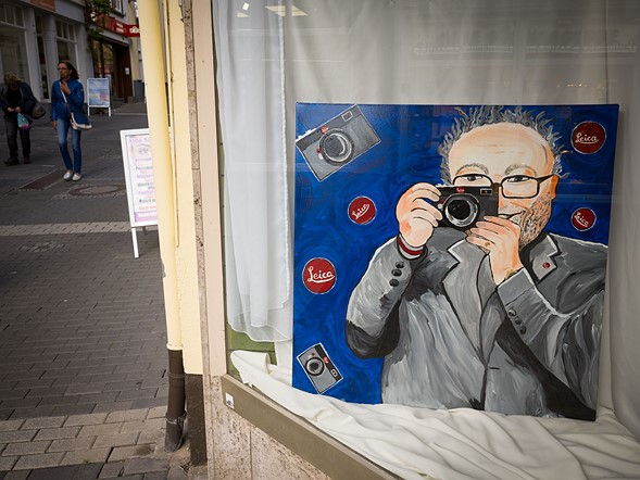 Leica được thành lập ở Wetzlar, và đặt trụ sở tại đây kể từ đó. Vì vậy, Leica có một liên kết chặt chẽ đến các hoạt động của thành phố, các quán cà phê, quán bar vì những người hâm mộ Leica sẽ đến hành hương về nơi khai sinh của công ty. Đây có thể là fan art mà tác giả tình cờ thấy được tại một cửa hiệu tranh ảnh tại trung tâm thành phố.