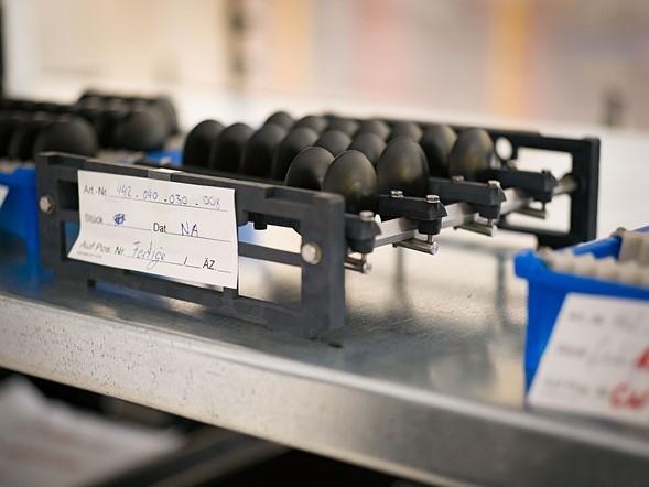 Quy trình sản xuất ống kính rất nghiêm ngặt. Các thấu kính từ những thấu kính thô qua các công đoạn xử lý đều được sơn một lớp sơn dầu bảo vệ màu đen và được tẩy rửa đi cho đến khi bắt đầu công đoạn tiếp theo. Chỉ sau khi quá trình đánh bóng cuối cùng kết thúc chúng mới được chuyển sang môi trường được kiểm soát nhiệt độ, độ ẩm để sơn phủ coat.