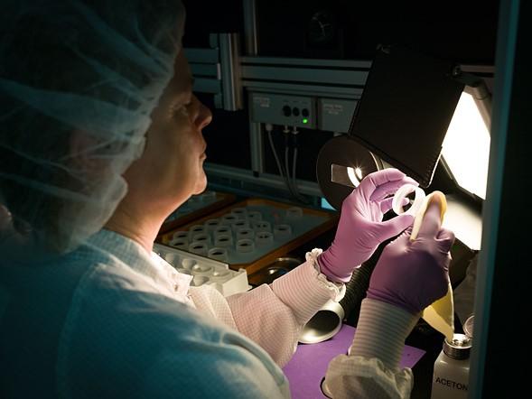 Một thấu kính được mài, đánh bóng và tráng phủ. Sau đó được kiểm tra và lau sạch bằng tay.