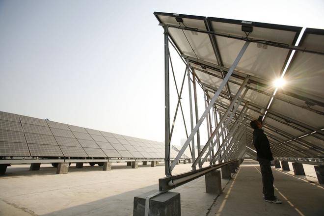 Một công nhân đang làm sạch các tấm pin mặt trời tại nhà máy sản xuất điện từ năng lượng mặt trời, được xây dựng từ ngày 3-11-2008 tại Tây Ninh, tỉnh Thanh Hải, Trung Quốc.