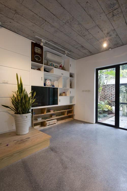 Sự đơn giản, dân dã của ngôi nhà thể hiện rất rõ qua việc sử dụng nội thất: sàn láng xi măng, trần bê tông, và bức tường gạch mộc