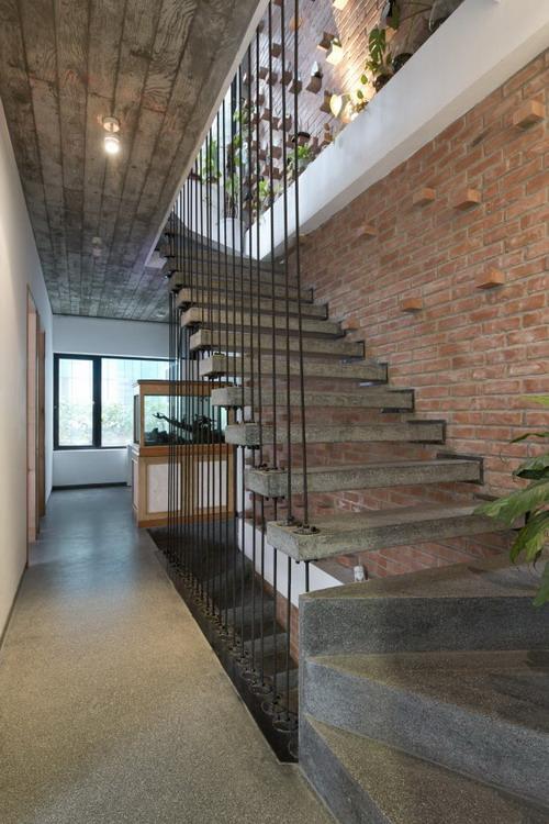 Bức tường gạch mộc xuyên suốt cầu thang từ tầng 1 lên tầng 4 tạo điểm nhấn bắt mắt cho ngôi nhà