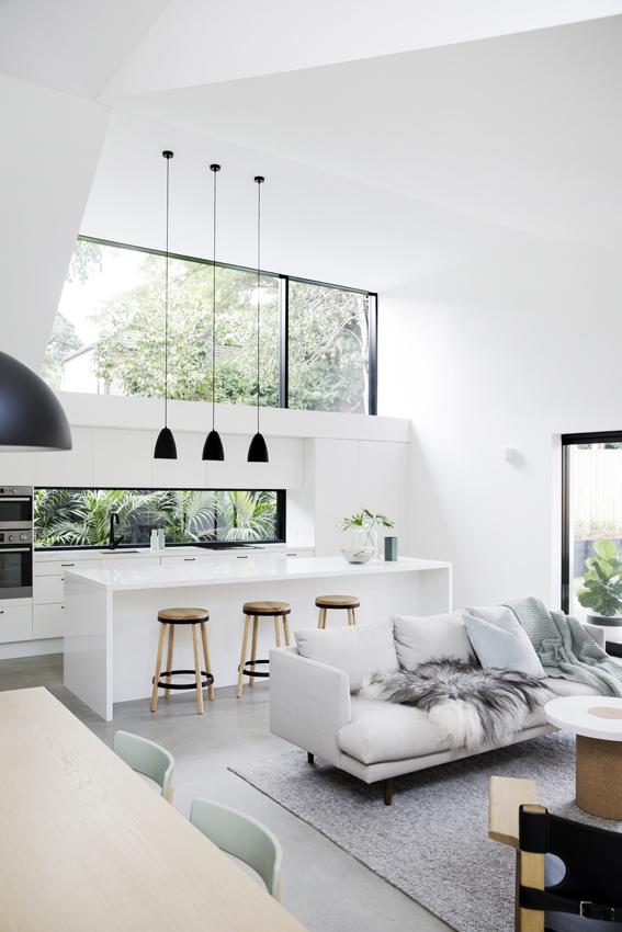 Nét độc đáo của ngôi nhà này đó là có rất nhiều cửa kính mang màu xanh thiên nhiên tràn ngập khắp không gian. Khu vực phòng khách ấm cúng với bộ salon đơn giản và thảm trải sàn.
