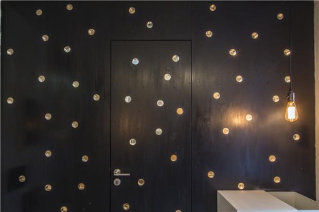 Ánh kim từ những miếng nhôm trang trí làm nổi bật khoảng tường màu đen