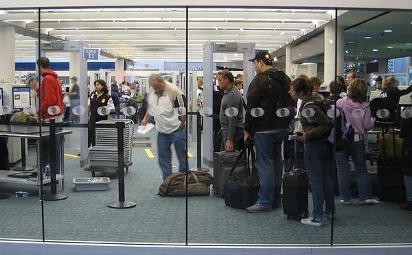 Các hành khách đang chờ để qua máy soi an ninh.
