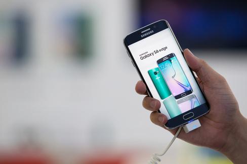 Một nhân viên giữ một cạnh điện thoại thông minh Samsung Galaxy S6 tại showroom của công ty ở Seoul, Hàn Quốc. Nhiếp ảnh gia: SeongJoon Cho / Bloomberg