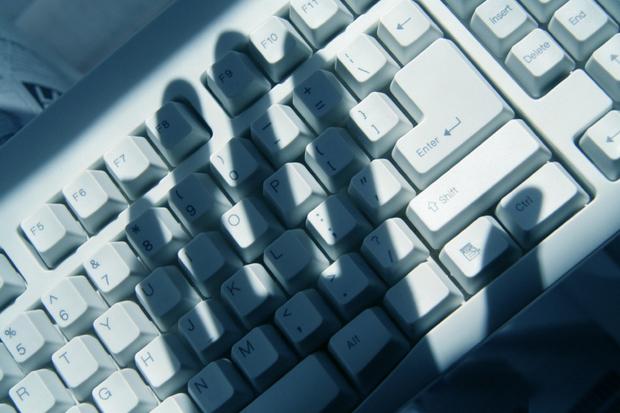 computer hacking hacker thief white collar crime stealing keyboard hand shadow 000001325773