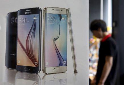 Một người đàn ông đứng cạnh một biểu ngữ quảng bá Samsung Electronics smartphone Galaxy 6 tại một cửa hàng ở Seoul, Hàn Quốc, ngày 7 tháng 7, năm 2015. REUTERS / Kim Hong-Ji