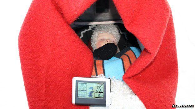 Một đứa trẻ ngủ trong xe nôi ngoài trời có gắn nhiệt kế điện tử trong thời tiết xuống tới -10°C.