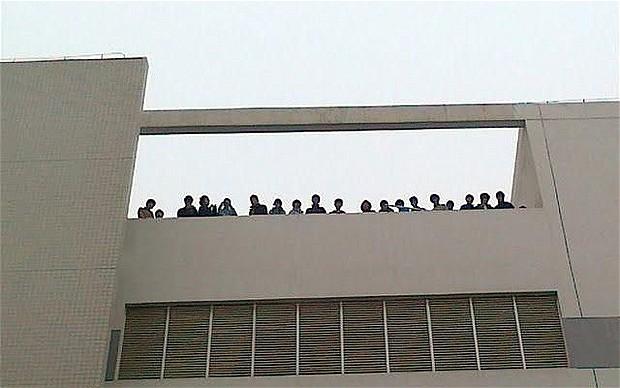 Những công nhân đe dọa tự tử bằng cách nhảy từ mái nhà, để phản đối điều kiện lao động.