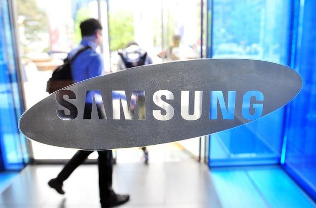 A visitor walks past the Samsung Electronics logo at the companys headquarters in Seoul on April 29, 2014