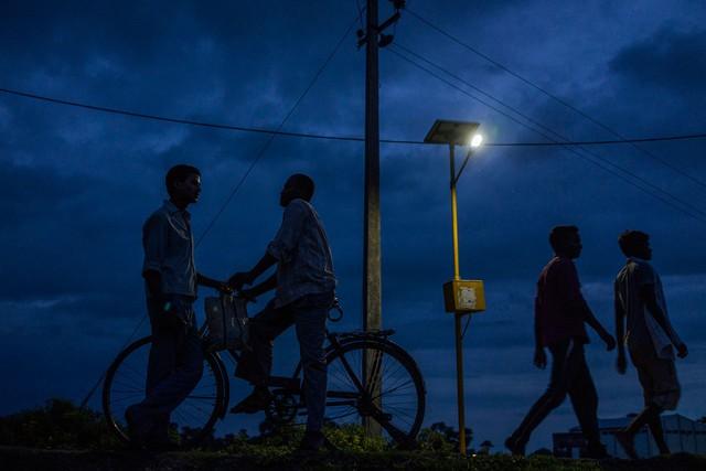 Dân làng Dharnai tại Jehanabad, Bihar, Ấn Độ đi lại dưới ánh đèn, được cấp điện từ năng lượng mặt trời, được ghi lại vào ngày 9/7/2015. Năng lượng mặt trời đang ngày càng được áp dụng rộng rãi tại nhiều nơi trên thế giới.