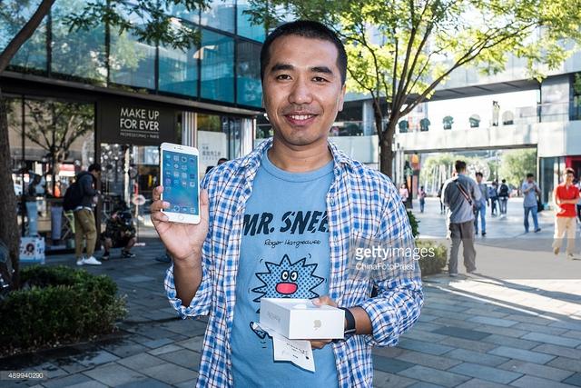 Một khách hàng khoe iPhone 6s mới trước cửa hàng Apple Store tại Bắc Kinh, Trung Quốc.