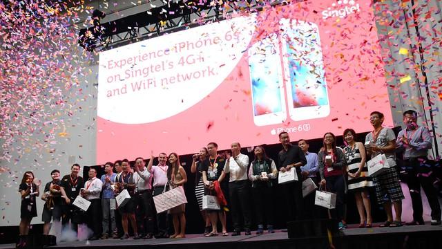 Daryl Lee (ở giữa đang cầm trên tay chiếc áo đỏ) là người đầu tiên trong dòng người tại Singapore được nâng cấp lên iPhone 6s.