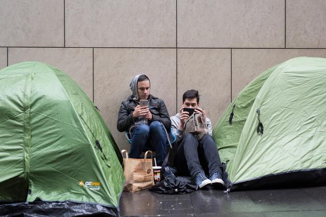 Chris Norton (bên phải) đã xếp hàng chờ mua iPhone mới từ khá lâu. Mặc dù thời tiết không ủng hộ nhưng anh và bạn bè vẫn cố bám trụ trong các túp lều dựng tạm trước Apple Store Úc.