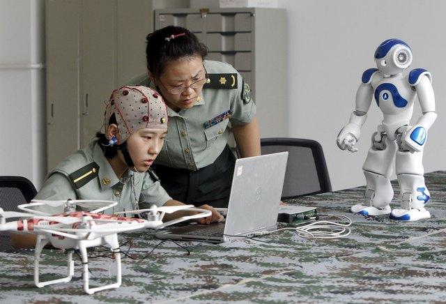 Một nữ sinh đang lắng nghe sự chỉ dẫn của giáo viên về cách sử dụng bộ thiết bị đeo để điều khiển robot tại trường ĐH. Kỹ thuật Thông tin PLA ở Trịnh Châu, tình Hà Nam, Trung Quốc. Ảnh Reuters.