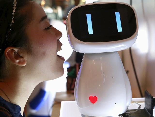 Một du khách đang nói chuyện với robot Xiaodu của Baidu tại Hội nghị Thế giới Baidu 2015 ở Bắc Kinh, Trung Quốc. Xiaodu là mẫu robot AI có khả năng truy cập vào cơ sở dữ liệu tìm kiếm của Baidu để phản hồi bằng giọng nói. Ảnh Tân Hoa Xã.