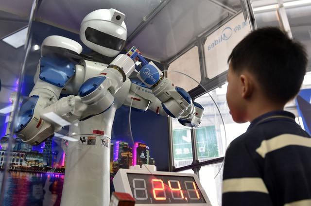 Một cậu bé đứng nhìn một chú robot đang giải khối rubic tại Triển lãm quốc tế Interet Plus Exposition ở Phật Sơn, Quảng Đông, Trung Quốc.