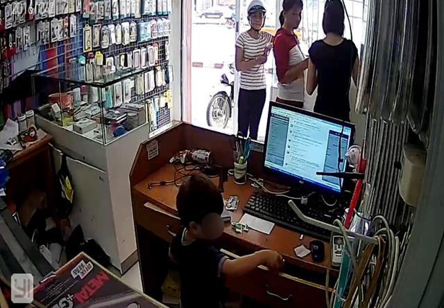 Bé trai lấy cắp điện thoại di động trong cửa hàng. Ảnh: Cắt từ clip.