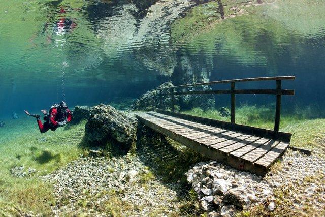 Cây cầu nhỏ xinh nằm trên những tảng đá lớn dưới nước.