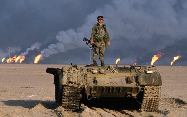 Một người lính Mỹ đứng trên chiếc xe tăng bị bắn hạ, sau lưng là những giếng dầu bị đốt đang nhả khói và lửa ngùn ngụt