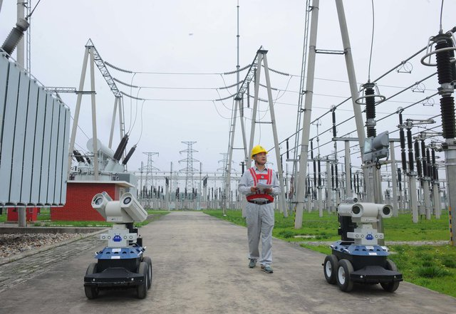 Một công nhân đang đi bộ cùng hai robot. Nhờ robot, con người không cần giám sát 24/24 nữa.