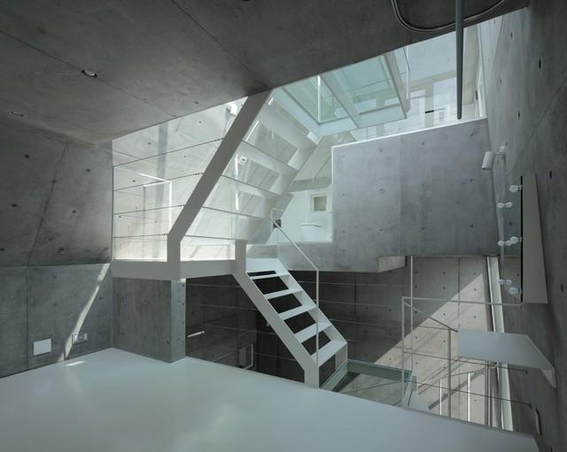 Những tia nắng mặt trời rọi xuống, len lỏi qua trần nhà tráng men và phòng tắm, qua cầu thang treo và sàn nhà bằng kính, chiếu sáng cho không gian sống với thiết kế chìm (sunken) của ngôi nhà nằm ở Tokyo này. Diện tích ngôi nhà chỉ vỏn vẹn gần 24m2, hoàn toàn vừa khít với vị trí góc phố siêu nhỏ.