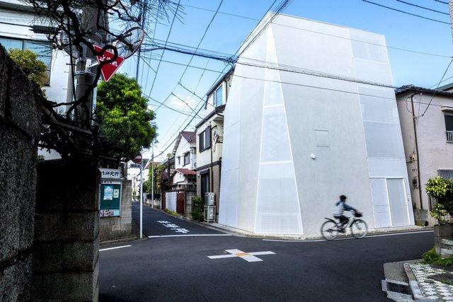 Với bức tường nghiêng được sơn trắng hoàn toàn, cửa sổ phủ kín, người ngoài khó có thể đoán được sự sắp xếp không gian nội thất cũng như tính tiện nghi của ngôi nhà này. Dù nằm ở vị trí ngã tư đường, ngôi nhà không hề gây cản trở dòng xe cộ di chuyển không ngớt xung quanh.