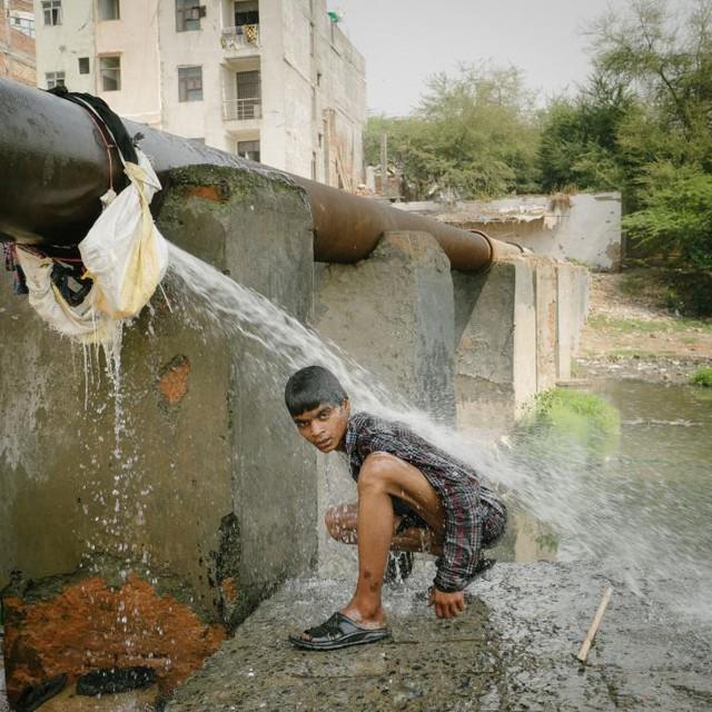 Một người bán ve chai đang rửa mình bên một cống thoát nước, nơi anh vẫn hàng ngày lùng bới đồ kiếm sống