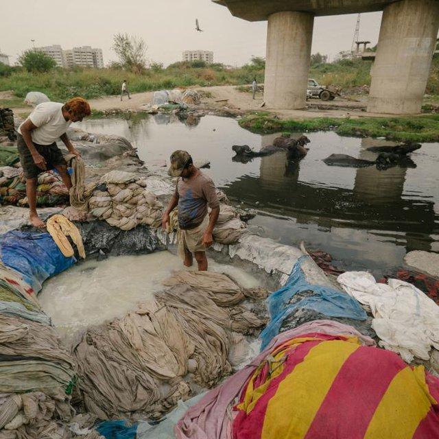 Những người đàn ông đang tẩy trắng quần áo trước khi đem xả lại chúng dưới con sông Yamuna ô nhiễm