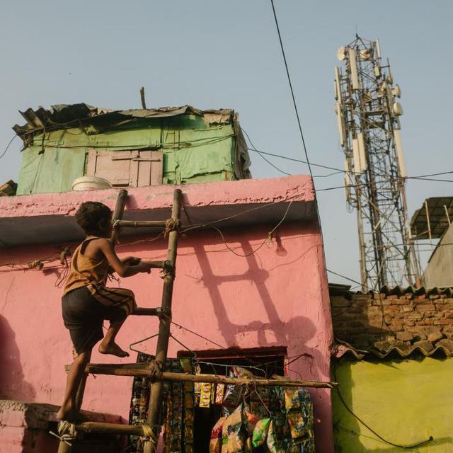 Một cậu bé trèo lên nóc căn nhà trong khu dân cư ngay cạnh cống thoát nước Shahadra