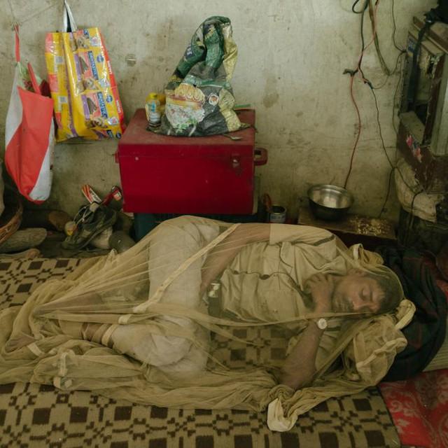 Sốt xuất huyết là một trong những căn bệnh vẫn đe dọa cuộc sống của các cư dân sống bên những con sông và cống thải ô nhiễm. Người đàn ông này nằm ngủ dưới lớp màn muỗi như một biện pháp chống đỡ.