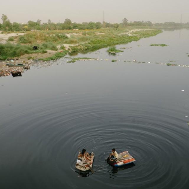 Trẻ em dùng xuồng lượn dọc sông Yamuna tìm kiếm những món rác thải có thể bán được