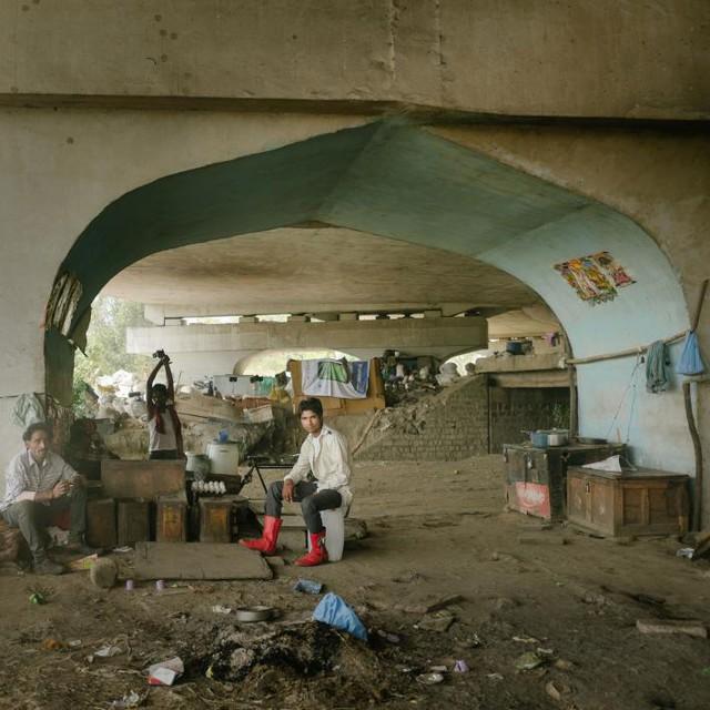 Những người buôn ve chai ngồi dưới gầm cầu chờ những người nhặt rác mang đồ đến để phân loại